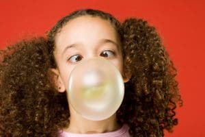 little girl blowing bubble gum bubble