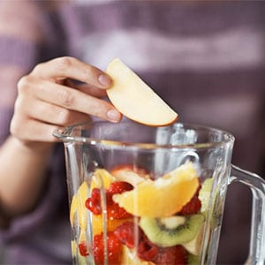 placing fruit into blender