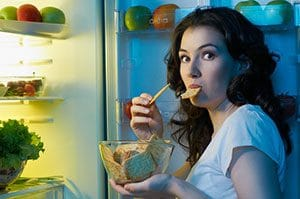 woman eating food from the fridge